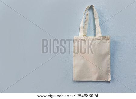 White Tote Canvas Fabric Eco Bag Cloth Shopping Sack On Wall Background / Zero Waste Use Less Plasti