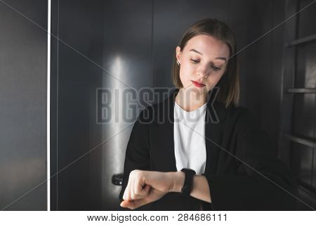 Punctual Office Worker Is Checking Time In The Lift. Young Woman Is Watching Her Clock To Check Time