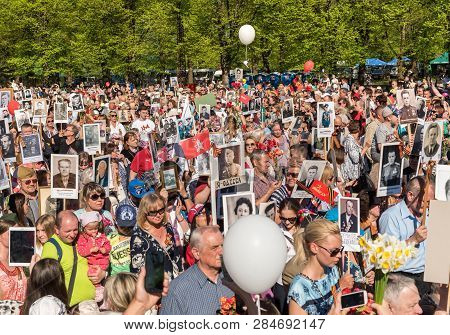Riga, Latvia - May 9, 2018: Procession Of People With Flags And Photos Their Relatives In Immortal R
