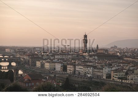 Landscape of the city of Florence, Italy on a long-focus lens, view from the playground on the Arno River and the Palazzo Vecchio in the evening sunset. poster