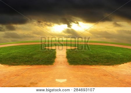 A Baseball field looking out to an endless curved horizon and a dark stormy sky.