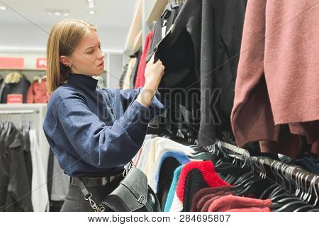 Attractive Girl In A Trendy Clothing Store Chooses Clothes. Girl Looks At Some Clothes, Shopping In