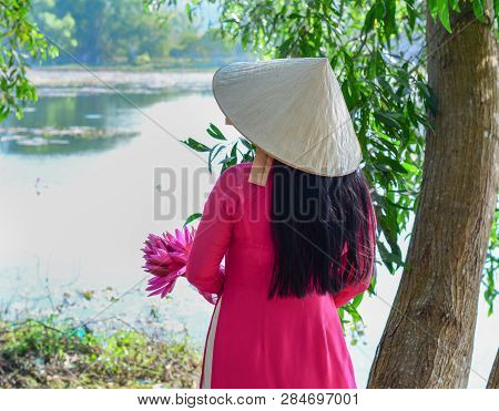 An Asian Woman In Traditional Dress (ao Dai) And Conical Hat With Waterlily Flowers.