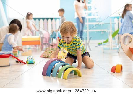 Kids Playing On Floor With Educational Toys. Toys For Preschool And Kindergarten. Children In Nurser