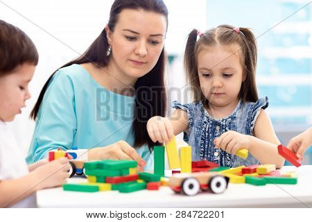 Little Children Building Block Toys With Carer At Home Or Daycare. Kids Playing With Color Blocks. E
