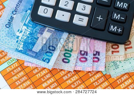 Qatar Riyal Bank Notes On Spreadsheet Report Background And Calculator