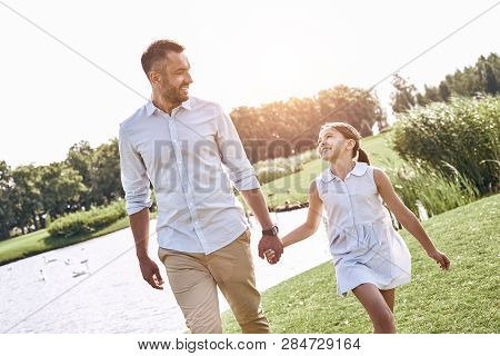 Single Parent, Father And Daughter Walking On A Grassy Field Hol