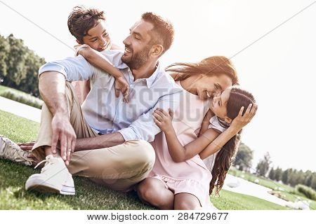 Bonding. Family Of Four Sitting On A Grassy Field Hugging Laughi