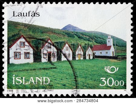 Luga, Russia - February 13, 2019: A Stamp Printed By Iceland Shows View Of The Turf Houses And Churc