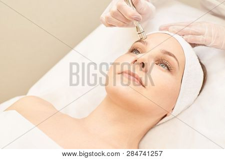 Electroporation woman face treatment. Facial rejuvenation therapy. Cosmetology skin spa equipment. Rf lifting. Massage device. poster