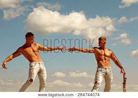 Testing Their Strength. Athletic Twins On Opposite Sides. Men Shows Off Their Strength Against Compe