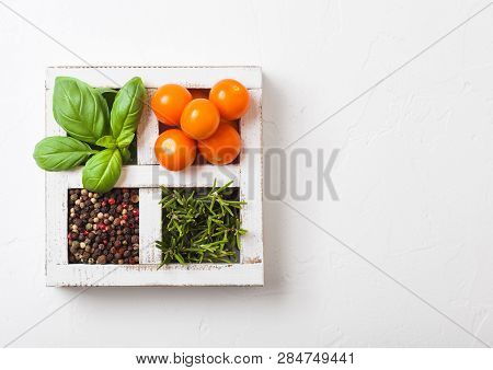 Organic Orange Rapture Cherry With Basil And Pepper And Rosemary In White Wooden Box On Stone Kitche
