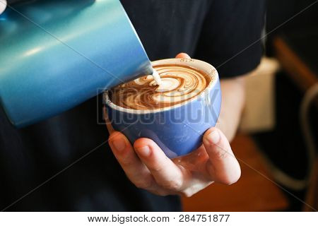 Barista Making Latte Art Focus In Milk And Coffee.hand Of Barista Pouring Milk Making Latte Frothy A