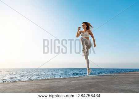 Young Motivated Happy Sporty Female Runner Fitness Instructor, Jumping, Excercise Near Sea Enjoying