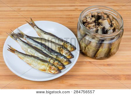 Smoked Baltic Herring On Saucer And Headless Baltic Herring Preserved In Vegetable Oil In Glass Jar