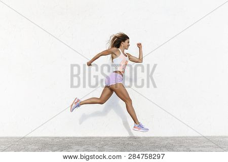 Strong Athletic Happy Sportswoman Wearing Sport Shorts Jump Across White Concrete Wall Facing Forwar