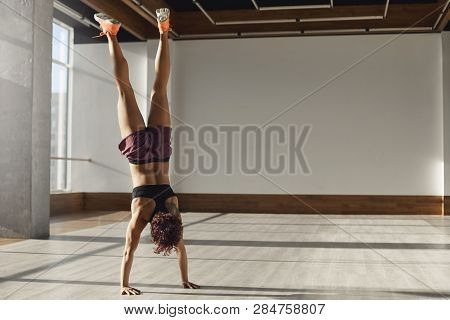 Strong And Motivated Young Sportswoman Making Handstand Focusing During Sport Excercises Training In