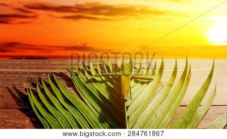 Cross Shape Of Palm Leaf And Palm Branches On Wooden Table With Rays Of Sunset Background. Palm Sund