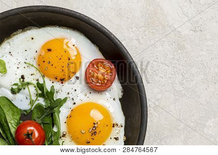Free Space With Fried Eggs With Herbs And Cherry Tomatoes On Pan. Left Edge Corner, Free Space