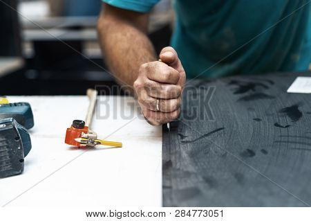 Manual wood concept. Cropped photo of cabinetmaker handcraft tradesman cut the surface of black mdf medium density fiberboard with special knife make furniture inside workroom poster