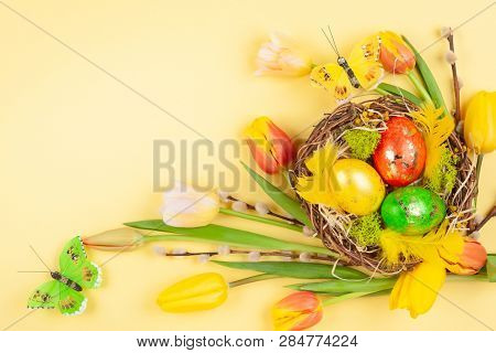 Easter composition with colorful Easter eggs in nest, spring flowers and branches of pussy willows on yellow background. Easter card with copy space. Top view. poster