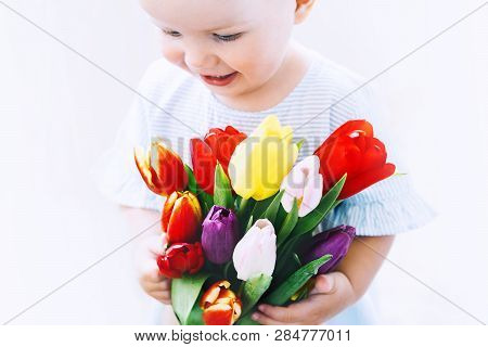 Cute Little Girl With Tulips Flowers
