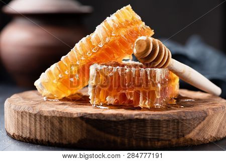 Honeycomb And Wooden Honey Dipper. Raw Honey. Natural Honey, Closeup View