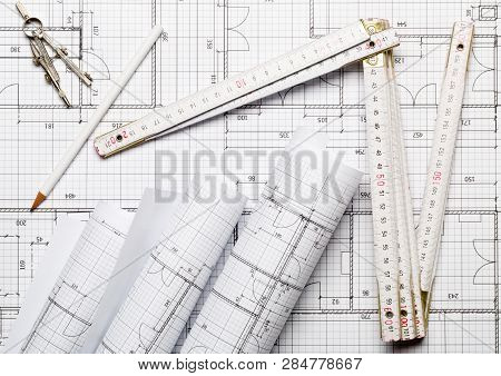 Rolls Of Architectural Blueprint House Building Plans On Blueprint Background With Folding Rule, Pen