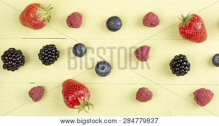 Soft Fruits Like Strawberry, Raspberry, Blackberry On A Green Wooden Table. Top View