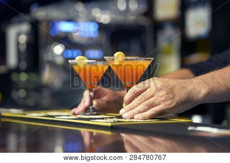 The Barman Gives Red Cocktail To The Client Of The Hotel Bar. Fresh Cocktail With Grapefruit. Alcoho