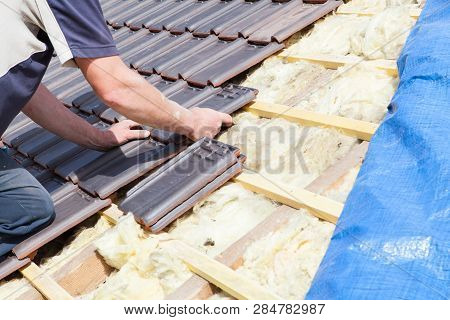 a roofer laying tile on the roof poster