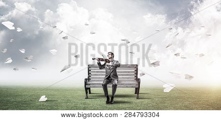 Young Man Wearing Suit And Glasses Sitting On Bench And Playing Violin
