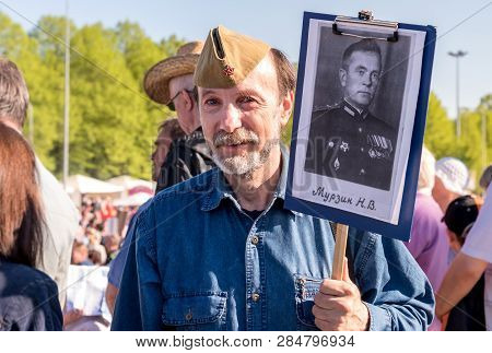 Riga, Latvia - May 9, 2018: Elderly Bearded Man With A Portrait Of His Relative In Immortal Regiment