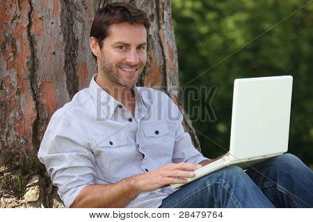 Mann auf Laptop außerhalb