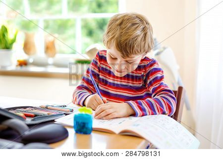 Happy Smiling Little Kid Boy At Home Making Homework At The Morning Before The School Starts. Little