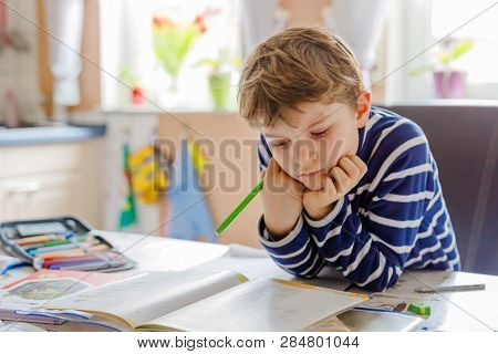Portrait Of Cute Happy School Kid Boy At Home Making Homework. Little Child Writing With Colorful Pe