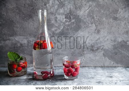 Strawberries In Water On A Dark Gray Background. Healthy Food, Fruit. A Bouquet Of Flowers As Decora