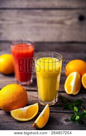 Orange Juice In Glass With Mint, Fresh Fruits On Wooden Background A