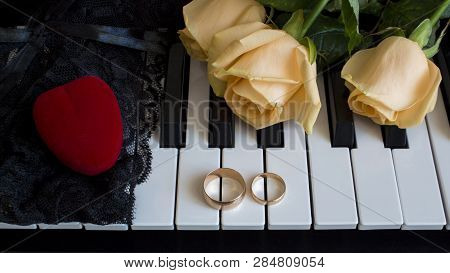 Gift To The Beloved Woman, Yellow Roses Lie On The Piano With Engagement Ring And A Red Box In The S