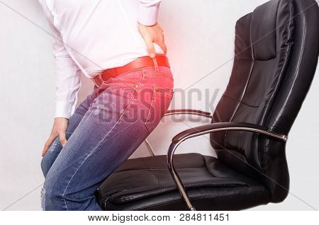 A Man In The Office Holding His Back From A Chair, The Concept Of Back Pain, Intervertebral Hernia A