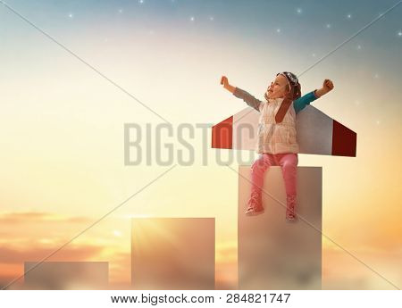 Little child playing pilot. Girl on the background of sunset sky. Kid in an astronaut costume dreaming of becoming a spaceman.