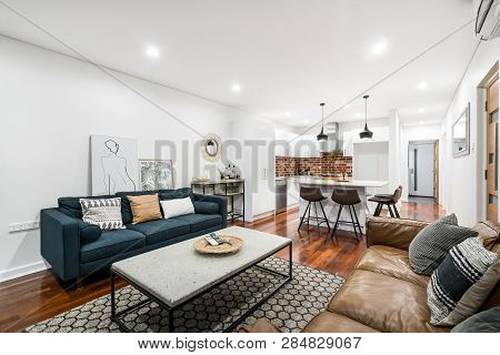 Living/dining room interior in modern Australian home with coffee table and modern industrial style decor. Perth, Western Australia. Photographed: February 2019.