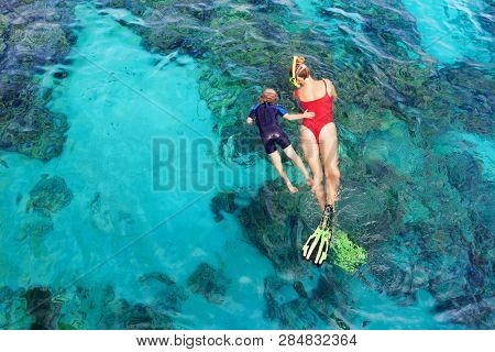 Happy Family - Mother, Kid In Snorkeling Mask Dive Underwater, Explore Tropical Fishes In Coral Reef