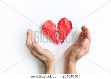 Red Crumpled And Broken Heart Shape Paper And Man's Hand