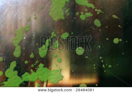 Green paint splatter on glass reflective surface poster