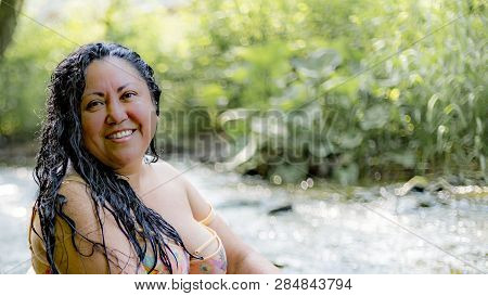 Sexy Mature Latin Mexican Woman With Long Black Hair Sitting With Wet Hair In A Calm Floating River,