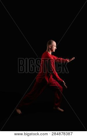 Man In Red Costume Practicing Qigong In The Dark