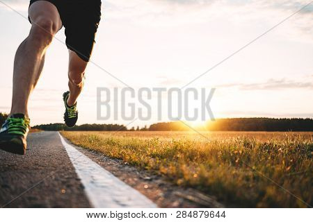 Fast Strong Runner Feet Running On Asphalt Road Close Up In Sport Shoe. Athlet Run Outdoor. Blurred
