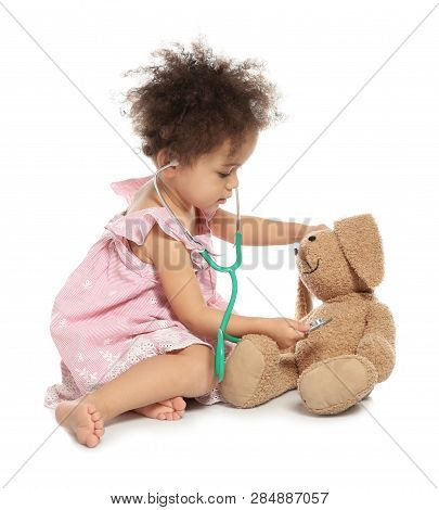 Cute African American Child Imagining Herself As Doctor While Playing With Stethoscope And Toy Bunny