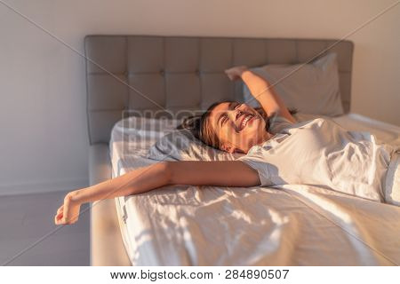 Happy woman lying in comfortable foam latex mattress bed in luxury hotel enjoying relax weekend getaway jumping in bed. Enjoying Asian woman with open arms in freedom.
